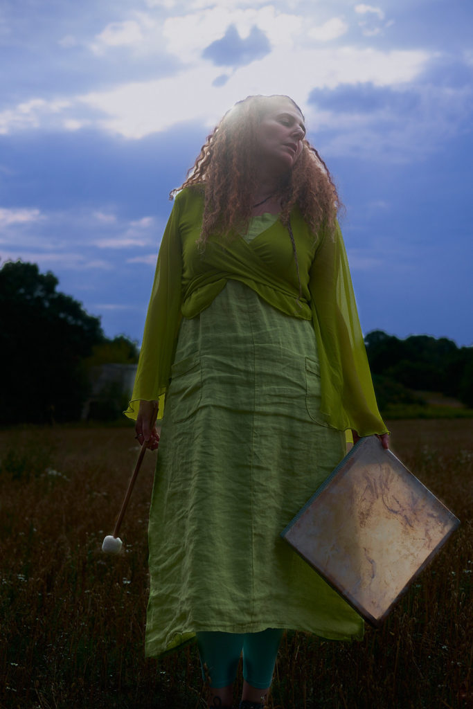 Raphaela Gilla on a summer meadow holding her shaman square drumm