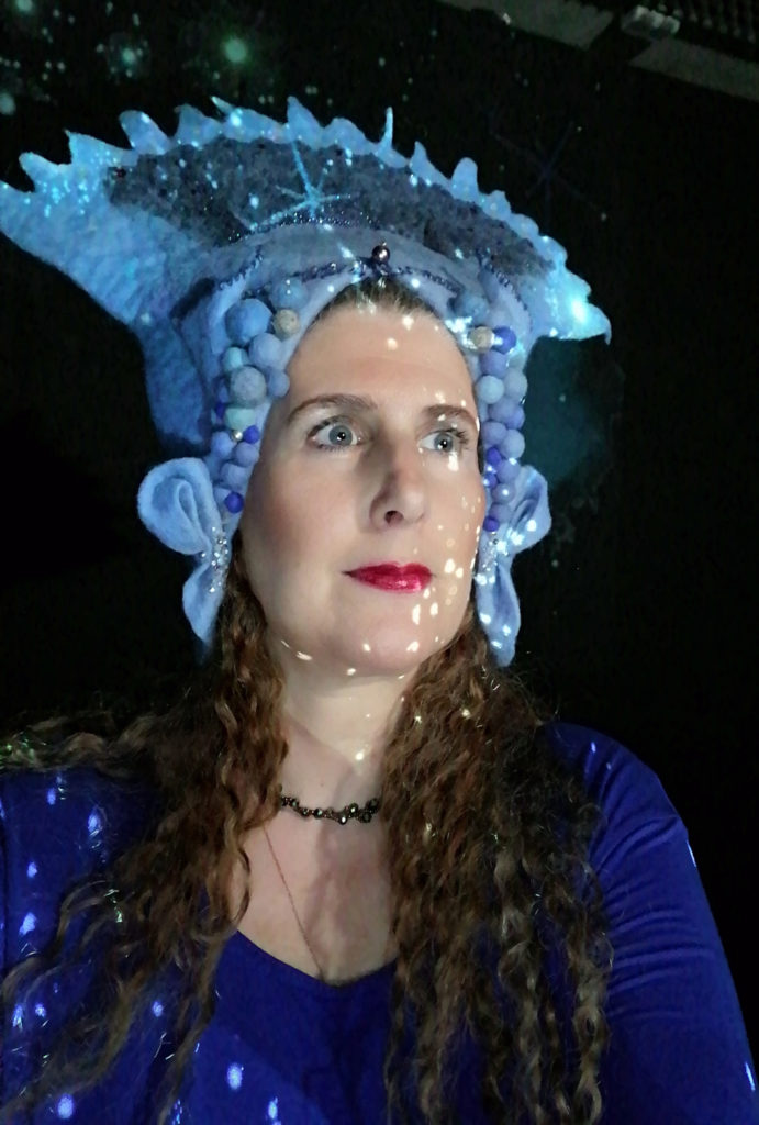 portrait of Raphaela Gilla at a live performance with her blue crown